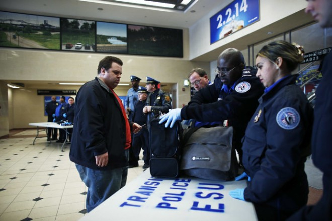 Members of the Transportation Security Administration check a passenger's bags with N.J. Transit Police to secure mass transit for the Super Bowl XLVIII, in Secaucus